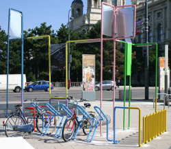 publicdesignfestival:  Almost a sculpture. This is the new bike parking station of Museumsquartier in Wien (Austria) designed by MN*LS and PPAG architects. The colorful wire hides a solar panel to turn on the LED lamps at nights, a tire pomp and a static bike with dynamo to produce energy while exercising/playing.   Love the inclusion of solar panels to keep it efficient.