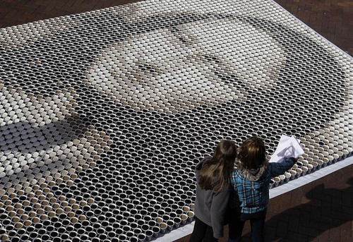 Artist assistants stand next to 3,604 cups of coffee which have been made into a giant Mona Lisa in Sydney, Australia. The 3,604 cups of coffee were each filled with different amounts of milk to create the different shades.