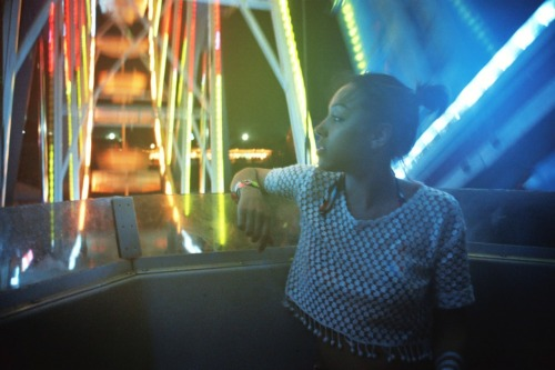 Running low on film on the ferris wheel. The last night of Coachella, four shots left before Kanye's set. Guessed aperture due to low light, rainbow glow and Kayla looking at the concerts below. This makes me so happy.