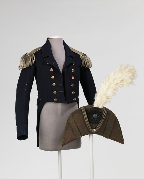 "c. 1776-83 According to the donor, this ensemble was worn by Obedeak [sic] Herbert, a Continental Naval Admiral of the Revolutionary War. This form of jacket, the tail coat, persisted first, as men's everyday wear and, later, as formal attire throughout the 19th and 20th centuries. The epaulettes retain sense of delicacy and refinement as handmade objects. The silk on the underside is padded and sewn into a roll at the edge to enhance the shape of the tassels as they fall over the shoulders. The tape on the other end is meant to tie into corresponding studs on the shoulders of the jacket. The phrase on the medallion of the bicorne, ""E Pluribus Unum"" (translated as ""Out of Many, One"") was submitted by the committee Congress as part of a design for the seal for the United States of America in 1776, which, upon revisions, was passed as the official seal in 1782. The phrase was considered the motto of the United States until 1956 when it was replaced with the motto, ""In God We Trust."""