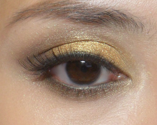 """Girl with the Golden Eye"" (Soft Yellow-Gold Shimmer) —-  Step 1: Sculpt your sockets with a soft brown. Note that if your lids are hooded, you should shade just above your socket line. —-  Step 2: Take any metallic yellow-gold eyeshadow (most brands will have a version), foil it, and apply it in soft circular swirls over your lids until you get the intensity you want. —-  Step 3: Apply black liner along the inner rims of your upper and lower lash lines, then pat matte black shadow over to set and intensify. Then gently trace the gold shadow over the lower lids as well. —-  Step 4: Apply false lashes or black mascara to finish the look. —- For the Lips: I chose MAC Angel lipstick, a soft pink-nude, and topped it with KATE Lip Gloss in PK-1, a very sticky, shimmery gloss in almost exactly the same shade."