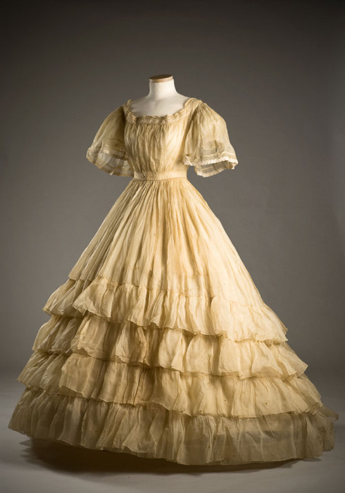 Starched organdy dress, 1865. Typical of mid-19th century styling, the very full skirt was worn over a hoop petticoat and is further widened by layers of ruffles. The starch used on this garment has discolored it over time.  This dress was worn by Marianna Heyward (b. 1844) when she married Benjamin Walter Taylor on December 14, 1865. They had eight children, including early 20th century artist Anna Heyward Taylor.  During the Civil War, Benjamin had served as a surgeon, becoming the Medical Director of the Calvary Corps of the Army of Northern Virginia.  HT 802 The Charleston Museum