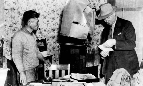 "An FBI agent looks for contraband at this Palos Verdes farmer's house, 1941.  Another Japanese local had been arrested for forgotten ammunition used for shooting rodents. Broken car headlights from an old car and an empty flashlight case were grounds for ""signaling the enemy."" In FBI reports, prefectural association membership was boldfaced. Almost all Issei belonged to these hometown organizations. (Photo courtesy of LAPL-NARA)"