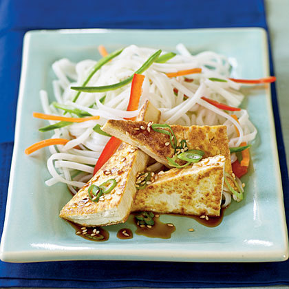tonedfitandfab:  Soy-Glazed Tofu Yield: 4 servings (serving size: 3 triangles) Ingredients 1 (12-ounce) package firm tofu, drained and cut crosswise into 6 slices  3 tablespoons seasoned rice vinegar  2 tablespoons fresh orange juice  2 tablespoons low-sodium soy sauce  1 tablespoon brown sugar  1/4 teaspoon grated orange rind  1 teaspoon dark sesame oil  2 tablespoons thinly diagonally sliced green onions  1/2 teaspoon sesame seeds, toasted  Preparation  Cut each slice of tofu in half diagonally. Place tofu slices on several layers of paper towels, and cover tofu with additional paper towels; let stand 15 minutes, pressing down occasionally. Combine vinegar and next 4 ingredients (through rind) in a small saucepan; bring to a boil. Reduce heat and simmer, uncovered, 6 minutes or until thick and syrupy. Heat oil in a large nonstick skillet over medium-high heat. Arrange tofu slices in pan in a single layer; sauté 5 minutes on each side or until golden brown. Remove from heat; pour vinegar mixture over tofu to coat. Sprinkle with green onions and sesame seeds. Serve immediately. Nutritional Information Amount per servingCalories: 132Fat: 6.5gSaturated fat: 1.2gMonounsaturated fat: 1.5gPolyunsaturated fat: 3.6gProtein: 8.9gCarbohydrate: 9.2gFiber: 0.1gCholesterol: 0.0mgIron: 1.8mgSodium: 419mgCalcium:68mg
