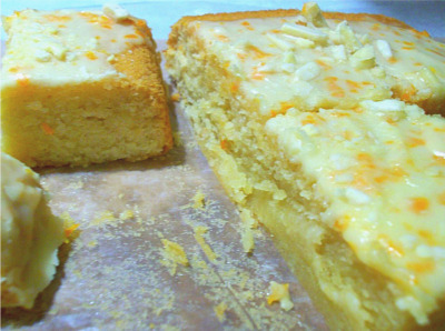 "Argentine Recipe: Orange Honey Almond Cake Recipe adapted and adjusted, original recipe ""Orange Cake"" adapted from Shirley Lomax Brooks's cookbook Argentina Cooks! My modifications were making half of the sugar honey instead. This created a denser, moister cake. I also topped the iced cake with chopped, shelled almonds. Another difference is that I used a standard 13 x 9 inch baking pan with the same temperature, but a slightly shorter time by five to ten minutes or so. Ingredients: 1 cup butter, softened 2 cups sugar 4 whole eggs plus 2 egg yolks 1 3/4 cups flour 1 1/2 cups blanched and finely ground almonds 2 cups confectioners' sugar grated rine of 1 orange 1/4 cup orange juice Directions: Preheat the oven to 300 degrees Fahrenheit. Cream the butter and gradually add the sugar. Beat the mixture until it is light and fluffy. Add whole eggs and extra yolks one at a time, beating well after each addition. Stir in the flour and almonds and pour the mixture into 9-inch tube pan lined on the bottom with waxed paper. Bake for 1 hour, or until a clean broom straw or wooden toothpick inserted in the center of the cake comes out clean. Turn the cake out on plate and allow it to cool. To make the frosting, mix confectioners' sugar with orange rind and orange juice until smooth. While still warm, spread the cake with the frosting. Serves 6 to 8."