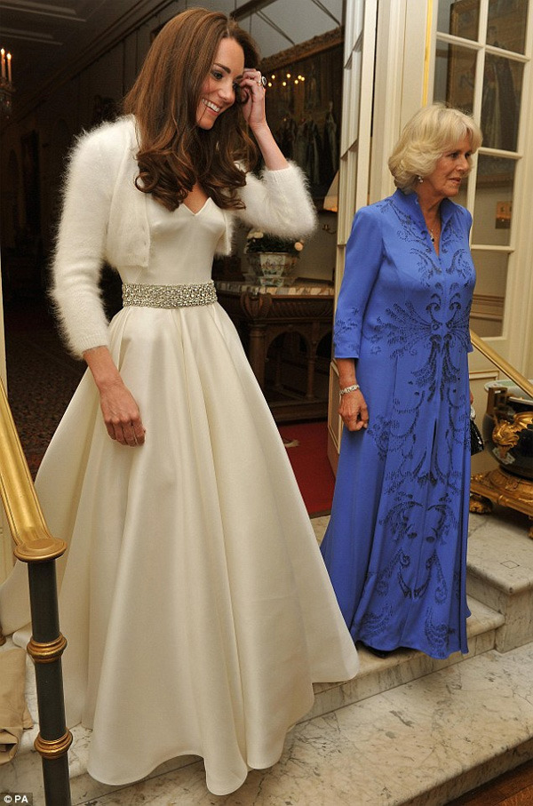 "Catherine Middleton's second wedding dress, another gown by Sarah Burton for Alexander McQueen. The Duchess of Cambridge changed into her ""disco dress"" for the evening soiree, a strapless white satin gazar evening dress with sweetheart neckline and diamante embroidered waist detail which she paired with a 3/4 sleeves cropped cardigan."