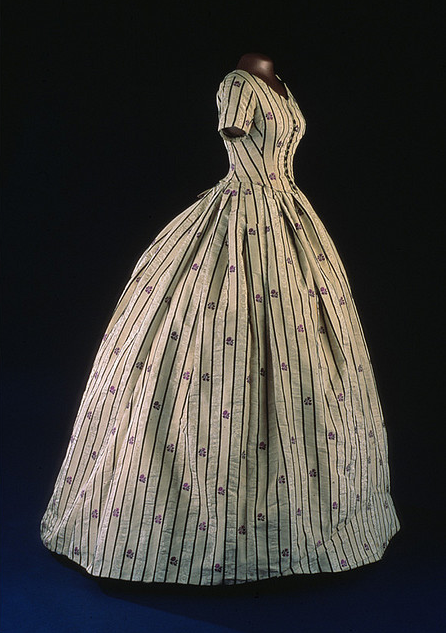 Mary Todd Lincoln wore this silk taffeta two-piece dress in 1861, with an evening bodice as the top piece. The pattern of black stripes and purple flowers is woven into the silk. Later in the 19th century, the original evening bodice was replaced with this daytime bodice made of fabric taken from the skirt.