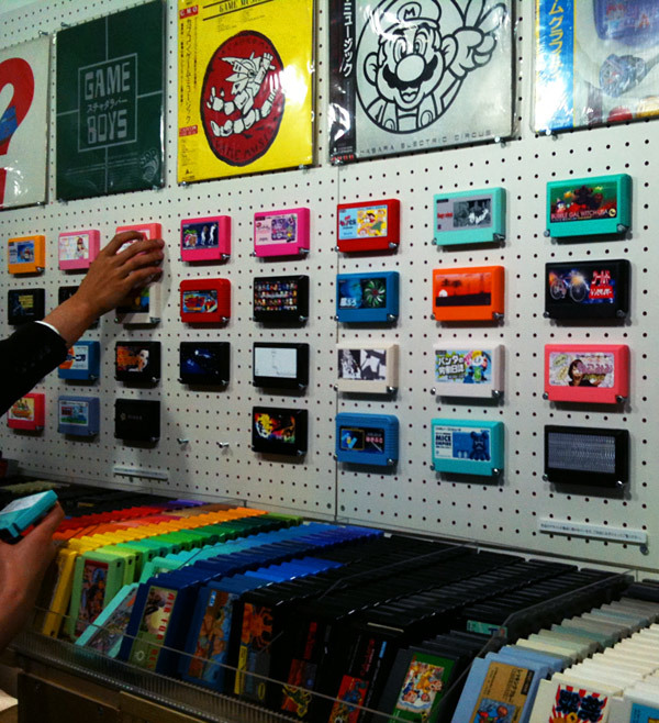 My Famicase Tease: wall of custom Famicom carts on display at Japanese video game culture shop Meteor. My Famicase Exhibition, the annual show featuring cartridge designs for game concepts created by artists around the world, opened in Tokyo today. The pieces aren't available to admire online yet, but folks who have visited the gallery are posting photos from the exhibit. If you look closely at the shot above, you can sort of see a tiny design for a cartridge sent in by a very special blog. Here's the list of this year's contributors, by the way. See also: Previous My Famicase Exhibition designs (must see), Our posts about the wonderful Meteor shop [Image via @kmpt]