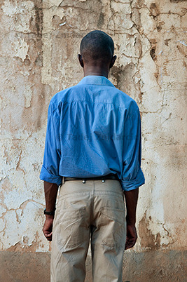 From Being Gay in Uganda, by Tadej Žnidarčič. Via Daylight Magazine.  Before you read our post, I recommend reading the interview at Daylight — it is informative, insightful, and direct. Discussions of work like this often get bogged down either in heavy theory or in a whole-hearted devotion to the documentary value that takes the nature of the photographs and the choices that shaped them as a given; neither is the case here.  In Being Gay in Uganda, Žnidarčič photographs gays and lesbians in Uganda. All of the photographs are posed in the same way, with the subjects facing away from the camera and toward walls, visible from around mid-thigh or knee up.  The photographer explains the choice of posing:     All the people I talked to wanted to remain anonymous so I portrayed them without compromising their safety. I didn't want to 'reduce' them to only their feet, hands or clothing, or hide their faces in one way or another. In this case, I think showing only their hands or clothing wouldn't say much about them and the situation they face every day. Since we see the 'complete' person, but the person is not facing us, the question arises: why can't they show their face? Why can't they face us? That's what I would like people to think about when they see these images.      Another element is that they stand in front of ugly, crumbling walls. These walls symbolize the obstacles they face and their exclusion from society.  That, and since the bill proposes the death penalty for homosexuals, a wall is something people get executed in front of. As a series, the portraits work as a group—unified by exact framing—in which each person is an individual, with his or her own posture, clothing, and accessories.   It is an interesting set of choices, addressing the strictly practical need to preserve subjects' safety, the portraitist's need to depict whole persons, rather than just parts that elude to a person, and also a symbolic function that the casual viewer might miss: the background as place of execution. (I confess, I did not initially make this connection when viewing the images.)  There are other consequences for these choices, which may or may not also be intended. The posing and framing are profoundly isolating, for example; the subject is cut off from the viewer by the pose and from the context by the framing. This is consistent with what the photographer is trying to communicate about the place of the homosexual in Uganda, but it does not hint at personal bonds, social networks, and organizations within the gay community (which exist and are referenced repeatedly in the interview); each subject stands alone.  I think this approach encourages a more typological and less personal viewing. Of course, there's nothing wrong with that, per se, but I wonder if the choice to represent one person against each wall, rather than two or several, was conscious and what governed it.