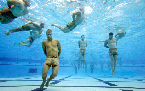 Navy SEAL trainees bounce off the bottom of the tank to catch their breath during the Drown Proofing Test at the Combat Training Tank. The trainees have their feet and hands tied and once freed they swim to safety.