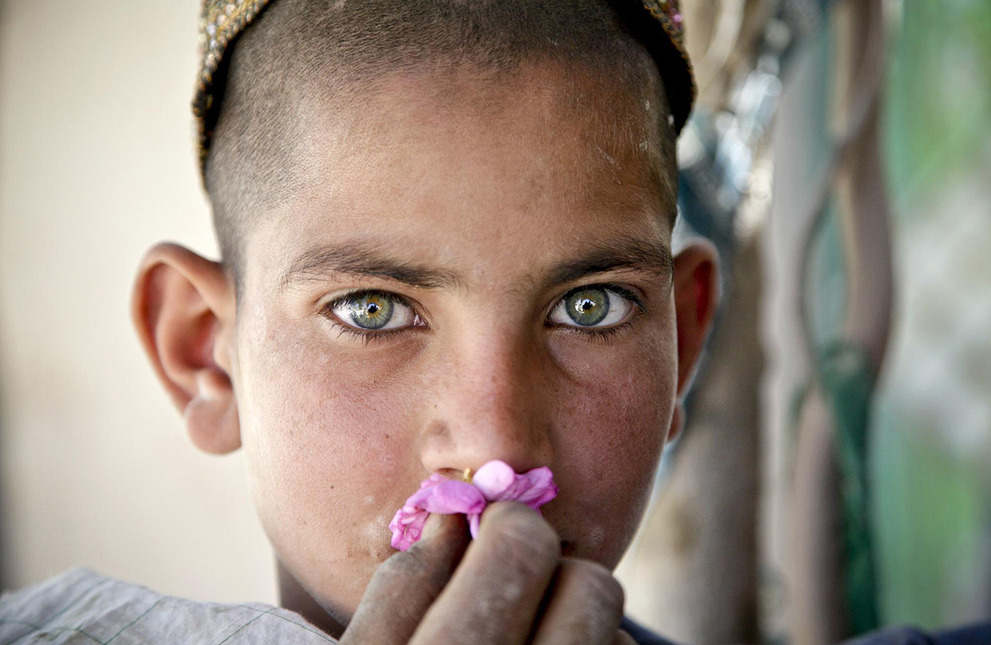 A  young Afghan boy smells a flower as he watches a Cultural Support Team  conduct an engagement with shop owners in the Oshay Bazaar, Uruzgan  Province, Afghanistan, on April 26, 2011.