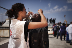doctorswithoutborders:  MSF medical staff treats a migrant after he survived a three-day boat journey from Libya. Generally, new arrivals suffered from seasickness, dehydration, hypothermia, and generalized body pain, such as headaches or abdominal pain. At the peak of arrivals in March, 3,000 migrants slept on the docks in Lampedusa for several days, sharing 16 chemical toilets and having access to only 1.5 liters of water per day. This was completely unacceptable. MSF Urgently Calls on Italian Authorities to Prepare For Influx Photo: Italy 2011 © Mattia Insolera