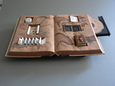 fullbloom:  This altered book by Meg Kennedy, found on the New York Center for Book Arts artist website, is altered into a mini curiousity cabinet displaying forms of media, with a little stone tablet, scroll, accordion book / pamphlet, Japanese-bound book, chalkboard, codex, and CD drive inserted into the open text block. The book is transformed into a cabinet, a display case, a bookshelf, and a sculpture, and it's still a book. (via Contained Herein by Meg Kennedy)  <3