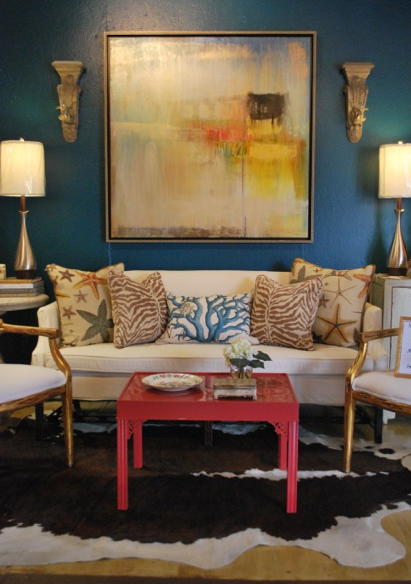 A beyond chic living room with peacock blue painted walls, gorgeous pillows, and a fab raw hide rug.