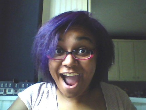 "For most of 2009 my hair was purple. I really loved my hair like that. I think I'll dye my bangs purple this year. Upkeep on a full head of purple hair is a pain in the ass, but it looks SO GOOD on me. In 2009, I worked at a ""professional,"" office job doing tech support, software QA & end user training. Why I dyed my hair purple was two-fold: I had really been wanting to dye my hair a fun color for a long time, and I had a hairstylist at the time who was totally game to do it. I was working for assholes. Okay #1 is pretty self explanatory, but let me lay down the boogie on #2. I was the only Black person in my office. They were owned by this rich right-wing conservative guy who was totally cool with having alcoholics and sociopaths work for him, but threatened to drug test us regularly. He said some subtly racist shit to me & my co-workers about Obama a couple of times, even though the people who worked in my department were obviously democrats and I was/still am very obviously a black woman. I wore my hair natural a lot. I also wore chucks, tee-shirts and other non-professional things. I mean, I wore dresses, slacks and cute stuff as I felt like it, but mostly I wore chucks and jeans. I'm really not one for dress codes unless there's a provided uniform. I'm gonna wear what's in my closet already.  Anyway, I'm awesome. Directly due to that I was eventually promoted to a position where I was out of the office a lot. I did software training with our clients [read: teaching middle-aged ladies how to use a mouse/windows/the internet]. They all loved me. I'm just as good at training as I am at getting strangers to like me & hear me out within a short period of time. Our clients were very happy. I got pulled into our HR manager/CFO's office once. She told me that my 'fro was unprofessional and that it was freaking out our clients. She wanted me to change it. At first I did nothing. I thought about what she was asking me to do and why. I guess she thought rural southern white folks might be intimidated by my curly fro. Maybe they thought I wasn't combing it or whatever they wanted to think about my hair… Maybe I was just TOO Black for her taste. At the end of the day, they totally learned everything I came to teach them, and most of them even ended up liking me & vice versa. So I really didn't see a problem with my hair at all. But I kept getting asked to change it. HR/CFO lady even offered take me to a ""Professional makeover workshop,"" where I'm sure they would have wanted me to get a relaxer. Fuck all that. So I went to my hairdresser and told her that I needed my hair flat ironed and dyed purple. It cost me about 90 bucks, and I got compliments from everyone, including my mom. I even let it fro out in the purple sometimes, which was ultra-cute. Here's your straight hair, CFO bitch. Professional makeover that."