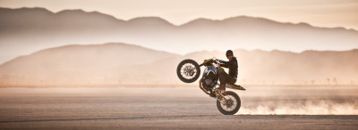 Jamie Robinson of MotoGeo doing a wheelie in the desert. This epic photograph was taken by Michael Svoboda.