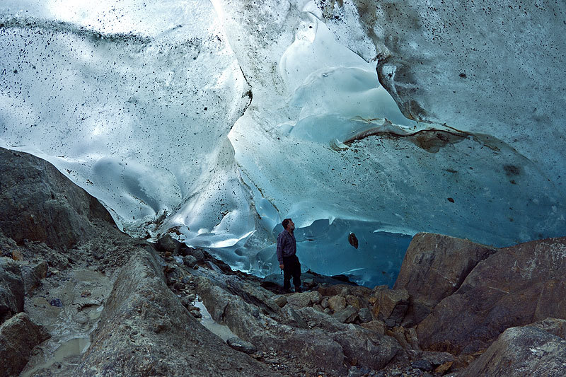 Small ice cave discovered below the location locally known as Chatzulecher, along the left margin of the Aletsch Glacier. This photo shows the lower end of the cave. Notice the rock embedded in the ice, in front of the person. Photo taken on October 13th, 2010. (via SwissEduc: Glaciers Online)