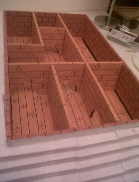 This is a photo of the basement section of my set model. This is the nome section under the floorboards. I have painted all the sections to look like wood and the doorways to look like mouse holes. I have also painted the exterior walls to look like brick. This photo also shows the steps which I have made to hide the basement section. The department store section will fit on top of this part. The different areas of the basement represent the different departments of the store and the different tribes of nomes that live in them.
