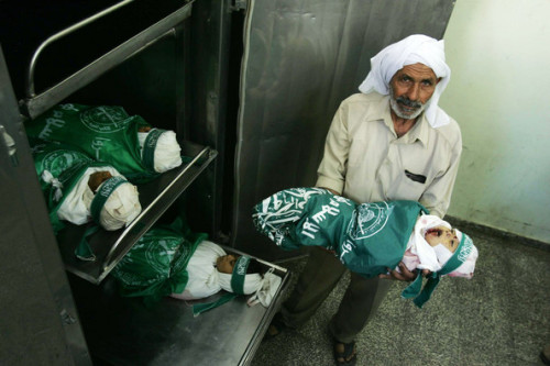palestiniangunmen:  A hospital worker carries one of four bodies of  young children on April 28, 2008 in Beit Lahia, Gaza. According a  medical source, their home was shelled on April 28, 2008, resulting in  the deaths of six Palestinians including four childern, their mother and  a Palestinian gunman. (April 28, 2008 - Photo by Abid Katib/Getty Images Europe)