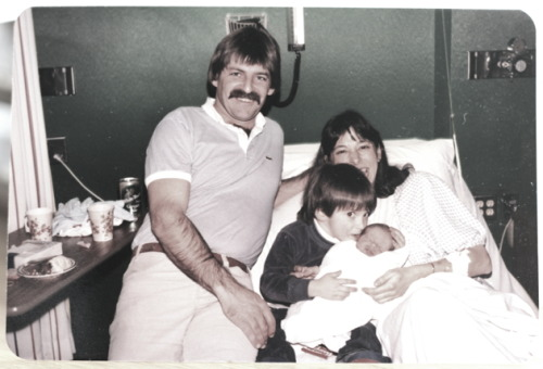 1987. Dad's moustache, mom & myself holding my little sister who was just born.