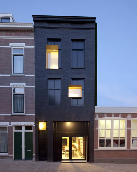 Studio Rolf.fr renovated a 100 year old, neglected Rotterdam house into something truly unique.  Here is the project description: The reconstruction of an old building in Rotterdam transforming it into my studio with house has resulted in an architectural spectacle in which has been experimented with space and time. The new metal window frames sticking out in some spots form a sharp contrast with the existing but freshly painted black facade and it's old windows that have been painted black as well. Announcing a new era with a entirely different way of living and working. On the inside all storyfloors and all the walls have been taken out reducing the interior to one big communicating space. Just as in the facade the traces of the past are visible everywhere in the interior as well. On the walls an old banister and holes of wooden floor beams reveal the partitioning of the former house. The new house and living space has a completely new interior arrangement.