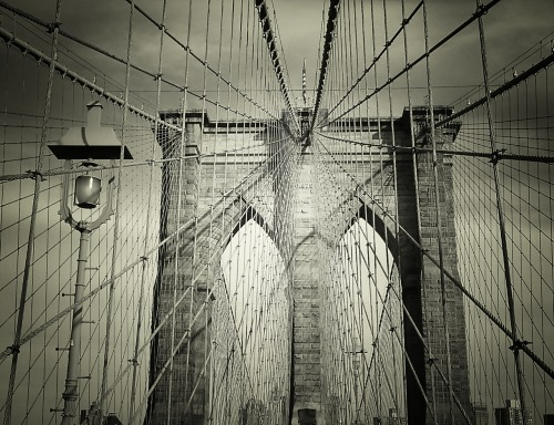 nythroughthelens:  The Brooklyn Bridge's cables and architectural elements. New York City. Last weekend, I walked to the Brooklyn Bridge to take in the sunset. I never take it for granted that I live in (relative) walking distance from one of the most photographed bridges in New York City. It's an iconic legend and everything anyone tells you about the bridge's views is absolutely true. It's equally breathtaking at sunset, sunrise and at night when the building's lights that make up the lower New York City skyline shine like a multitude of twinkling stars. What I love most about bridge walks here in New York City is the changing view and the vantage points over the river. Brooklyn Bridge is also stunning due to its structural and architectural elements. It's hard not to gaze up in wonder at the cables which lead the eyes towards its beautiful arches. There is always one point in my bridge adventures where I spend far too long with my head thrown back gazing up at these sorts of things that I almost tip over. Thankfully, I am usually not the only one experiencing this silly dizzying phenomenon ;). — You can now also view a gallery page for my New York City posters: New York City Posters by NY Through The Lens. Check it out!