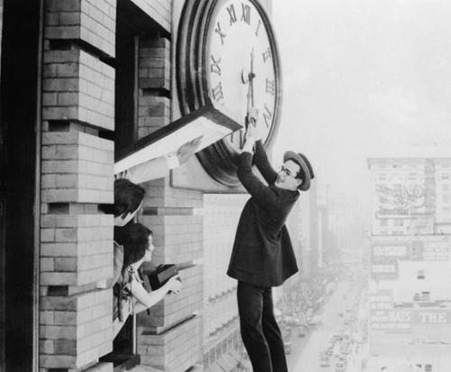 "miklem:  Hey everyone, it's 4/20, you know what that means: Harold Lloyd's birthday!! (via mothgirlwings & fyeah-haroldlloyd)  Harold Lloyd holds the hands of the clock in ""Safety Last"" while a young fan snaps a photo with a Brownie camera - March 23rd, 1923"