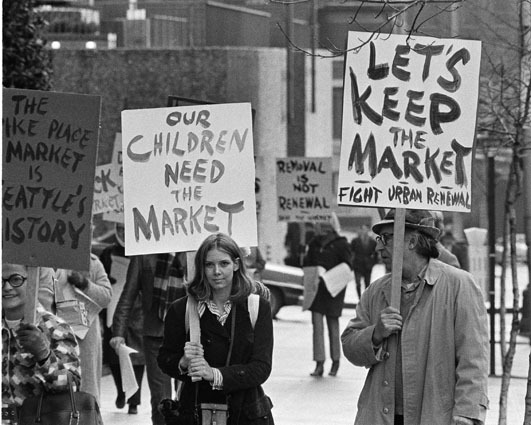 "mohai:  Demonstration Against Demolition of Pike Place Market, Seattle, 1971 Demonstrators march in a successful campaign to ""Save the Market"" from demolition. Seattle voters showed their support on November 2, 1971 by passing Initiative No. 1 that opposed the City Council's plan to raze the Market and build high rise offices and apartments with federal urban renewal funds. Photographer: Timothy Eagan Image Date: 1971 Image Number: 1986.5.53773.1  To order a reproduction or to inquire about permissions contact photos@seattlehistory.org or phone us at 206-324-1126. Please refer to the Image Number and provide a brief description of the photograph.   Contrary to my first impression, these are not protestors being ironic by supporting a neo-liberal, pro market philosophy. They are actually trying to save the  historic farmers market in downtown Seattle. They were successful, the Pike Place Market is thriving and is the number one tourist destination in the city."