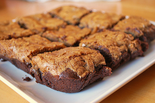 prettygirlfood:  Chipster Topped Brownies  For the brownie layer:6 ounces bittersweet chocolate, coarsely chopped 3 ounces unsweetened chocolate, coarsely chopped 2 sticks (8 ounces) unsalted butter, cut into chunks 1 2/3 cups sugar 4 large eggs ½ teaspoon salt ½ teaspoon pure vanilla extract 1 cup all-purpose flour 1 cup walnuts, coarsely chopped For the cookie layer:1 ¼ cups all-purpose flour ½ teaspoon baking soda ½ teaspoon salt 1 ½ sticks (12 tablespoons) unsalted butter, at room temperature ¾ cup (packed) light brown sugar 2/3 cup sugar 1 large egg 1 egg yolk 1 teaspoon pure vanilla extract 6 ounces bittersweet chocolate, chopped into chips, or 1 cup store-bought chocolate chips Center a rack in the oven and preheat the oven to 350 degrees F. Butter a 9-x-13-inch baking pan, line it with wax or parchment paper and butter the paper. Put the pan on a baking sheet. To make the brownie batter:Put both chocolates and the butter in a bowl set over a saucepan of simmering water. Stirring occasionally, heat just until the ingredients are melted, shiny and smooth. If the mixture gets too hot, the butter will separate from the chocolates. Remove the bowl from the heat. Working with a stand mixer, preferably fitted with a paddle attachment, or with a hand mixer in a large bowl, beat the sugar and eggs on medium-high speed for about 2 minutes, until pale, thick and creamy. Beat in the salt and vanilla extract. Reduce the speed to low and mix in the melted chocolate and butter, mixing only until incorporated. Scrape down the sides of the bowl with a rubber spatula, then, still on low speed, add the flour, mixing only until it disappears into the batter. Using the spatula, fold in the walnuts, and scrape the batter into the prepared pan. Set aside. To make the cookie dough:Whisk together the flour, baking soda, and salt. Working with a stand mixer in the cleaned bowl or with the hand mixer in another large bowl, beat the butter and both sugars together on medium-high speed until smooth and creamy, about 3 minutes. One at a time, add the egg and the yolk, beating for 1 minute after each addition. Beat in the vanilla. Reduce the mixer speed to low and add the dry ingredients, mixing only until they disappear into the dough. Still on low, mix in the chopped chocolate. Drop the cookie dough by spoonfuls over the brownie batter an, using a spatula and a light touch, spread it evenly over the batter. Bake for 50 to 55 minutes, or until the cookie top is deep golden brown and firm and a thin knife inserted into the brownie layer comes out with only faint streaks of moist chocolate. Transfer the pan to a rack and cool to room temperature. When the brownies are completely cool, carefully run a knife between the sides of the pan and the brownies, then invert them onto another rack, remove the paper and turn right side up onto a cutting board. Cut into bars about 2 inches by 1 inch.