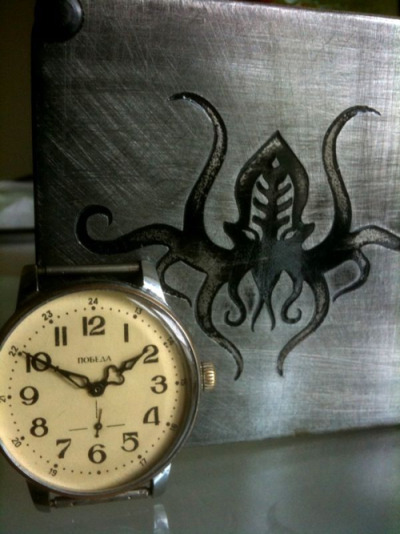 Submitted by thisiscorrect:  My logo acid-burned into steel, for my watch restoration business OctopiWWC.  That's a pretty rad design