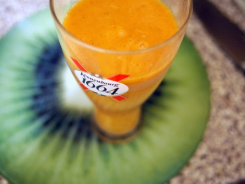 Tangy Tropical Smoothie a banana a kiwi a carrot juice of 2 oranges a squeeze of a lemon BLEND (look at my awesome kiwi chopping board glass thingy)