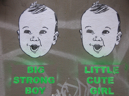 "practicalandrogyny:  [Stencilled graffiti showing two identical smiling babies' faces. One captioned ""BIG STRONG BOY"", the other ""LITTLE CUTE GIRL""]"