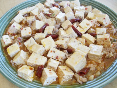Chinese Recipe: Mapo Dofu Adapted from the cookbook The Seventh Daughter by Cecilia Chiang. This is a famous and popular Sichuan specialty dish. It is also very easy to make. Rice is often served as an accompaniment to this dish. Ingredients: 1 teaspoon black bean sauce 1 teaspoon Shaoxing wine 1 tablespoon soy sauce 4 teaspoons minced garlic 2 tablespoons peanut oil 1/4 pound ground pork shoulder 1/4 cup, about 1 ounce, minced zha cai 16 ounces silken tofu, water drained off and cut into 1 by 2-inch cubes 1 teaspoon chili oil Pinch of ground Sichuan peppercorns or white pepper 1 tablespoon minced green onion plus a little extra for garnish Directions: To make the sauce, whisk together the black bean sauce, wine, soy sauce, and 1 teaspoon of the garlic in a small bowl. Set aside. heat a large wok over high heat until a bead of water dances on the surface and then evaporates. Add the oil and swirl to coat the pan. Add the pork and stir constantly, breaking the meat apart with a spoon. Toss in the remaining 3 teaspoons garlic with the zha cai and continue to cook until just a trace of pink remains in the pork, about 2 minutes. Using a spoon, very gently add the tofu to the pan. Quickly stir in the reserved sauce, then the chili oil, and top with Sichuan pepper and 1 tablespoon of the green onion. Immediately remove from the heat and serve on a platter with the green onion garnish. Serves 4-6 as part of a Chinese meal or 2-4 as a Western-style side dish.