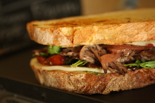 """Short Rib Panini with pickled red onions, fontina cheese, argula and roasted tomatoes."""