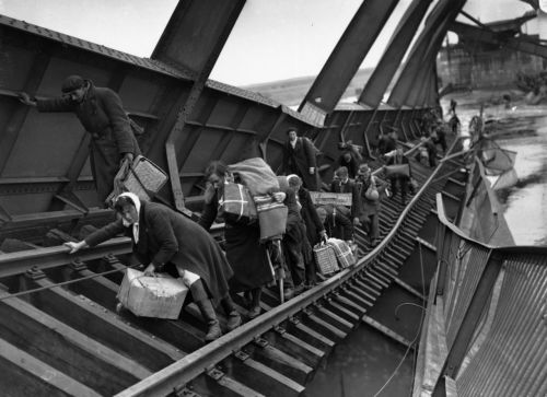 Displaced Persons crossing a bridge on the River Elbe at Tangermunde,  which has been blown up by the Germans, to escape the chaos behind  German lines caused by the approach of the advancing Russians, 1st May 1945
