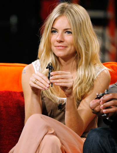 Sienna Miller holding up an action figure depicting her GI JOE: THE RISE OF COBRA character, The Baroness.   Sadly the action figure does NOT look a thing like her or her movie character. It was really really poorly done.   (via Getty Images)