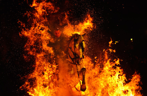 sun-star-n-moon:   A  man rides a horse through a embers and flames of a bonfire in San  Bartolome de Pinares, Spain on Saturday, Jan. 16, 2010, in honor of  Saint Anthony, the patron saint of animals. (AP Photo/Daniel Ochoa de  Olza)  (Click through for more amazing pics)