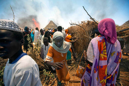newsflick:  Kuma Garadayat, Sudan: Women and children flee from a fire. (Reuters)