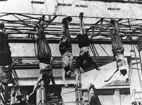The corpse of Italian fascist leader Benito Mussolini (1883-1945) hanging by his feet a petrol station in the city of Milan after being caught and executed by Italian partisans at Mezzegra on the 29th of April. The bodies are labeled on the photograph from left to right: Nicola Bombacci, Gelormini, Benito Mussolini, Clara Petacci (Mussolini's mistress), Alessandro Pavolini and Achille Starace.  Other sources state the man to the left of Mussolini as being Starace.
