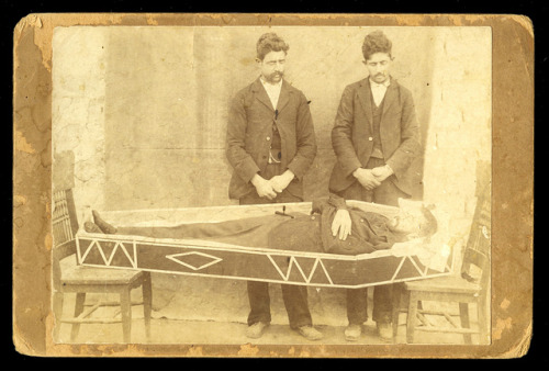 From Ballyhooligan on Flickr:  Post mortem cabinet card of a man in a coffin with two men standing watch overhead. Coffin is resting between two chairs. I believe this is Italian in origin. Some text is on the verso of the image, however, some silverfish damage has made most of the text illegible.