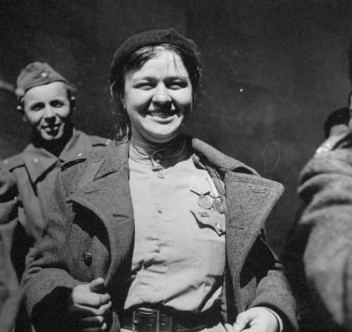 Female Russian soldier  grinning broadly while showing off her medals and a US Army Officer's  insignia pinned to her shirt after the Allied troops met following the  fall of Berlin, July 1945.