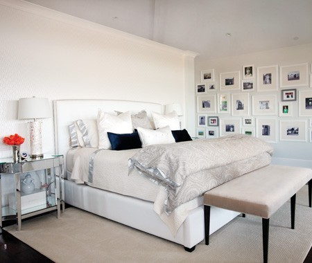 A white bedroom with mirrored furniture and a great gallery wall.