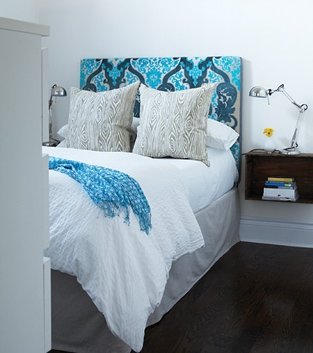 A turquoise and navy upholstered damask print headboard make this room pop!