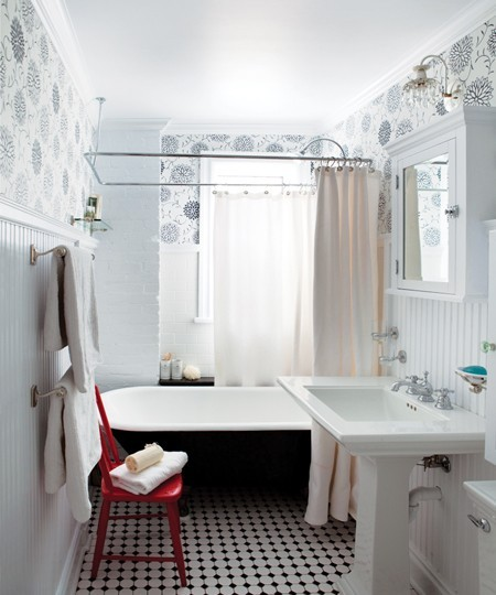 A wallpapered bath with a great tiled floor and a fun red chair!