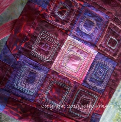 Magazine Carrier Tote Bag Made of Batik in Purples and Deep Reds OOAK by Julie Clark Art Unique magazine carrier tote bag made of batik fabrics in purples and  deep reds is handmade and one of a kind. Made of imported batik fabric,  this richly colored bag, saturated with purple, pink and deep red hues,  is perfect slung over the shoulder, carrying anything from magazines to  your slim book reader. Lined with cotton batting covered by a light  purpley-pink fabric, darker raw-edged strips allow you to tie this  unique bag closed.The focus of the bag is the patch-work of  batik fabrics, with wonky squares sewn onto the surface using my hands  to freely manipulate the fabric under the needle. The design is entirely  original, using many different threads, and is, indeed, one of a kind.SIZE:  The bag measure approximately 12 by 10-3/4 inches, and is about 2-1/2  inches wide (deep). For a better visual, it is a perfect size for  carrying standard-sized magazines. The strap is 37 inches long, so some  might be able to wear it sling-style. CARE: Spot clean only.The top edges are rolled under, and the entire piece is made by me, by hand.Kindly  keep in mind that as much as I try to describe pieces accurately,  computer monitors and resolution vary from machine to machine.
