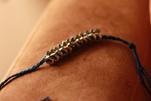 Whipped up the hex-nut braid bracelet that's been floating around Tumblr. I really love the way it looks. It took me a lot longer than I expected to complete! Part of that was my own fault; I wanted to use a royal blue crochet cotton instead of regular twine, and the cotton was so thin that I actually had to braid strands of it in order to make a cord thick enough to make the bracelet with. So I had to start out by making three braids, which took time because I wanted to make them fairly tight. It was also harder than I thought to keep it straight. Once you threaded a nut completely on, you needed to keep your thumb there to hold it in place. Ultimately what I wound up doing was wrapping tape around the ends of the strands to make a stiff tip; then I'd use the tip to kind of stab into the center of the hex nuts, so I didn't need two hands to thread them on. I kept my left thumb at the top to keep everything tight, and used my right hand to stab into a nut, then bring the strand up above my head and let gravity do the work of bringing the nut down to where my thumb was. Then — (this was important) — when I had to slide the nut into place behind the protective barrier of where my thumb was, I ONLY let go of the strand that the new nut was on. (I found that lifting up my thumb entirely to settle everything together was a surefire way to let everything fall out of order.) Anyway, it's a pretty simple concept once you find a comfortable way to keep everything tight! I recommend trying it.