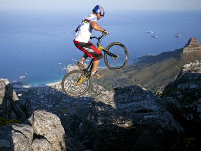 "Extreme Photo of the Week: Biking South Africa's Table Mountain ""Riding on top of Table Mountain was something I had to do,"" says professional mountain biker Kenny Belaey. ""The landscape is just perfect for trials—but I had to be really careful."" Belaey pulled out every daredevil trick imaginable, from wheelies to bunny hops, to explore the famous 3,558-foot slab of granite overlooking Cape Town. To reach the top at sunrise, he hiked through the night, carrying his 20-pound bike on his back. Photograph by Nick Muzik, Caters News Agency"