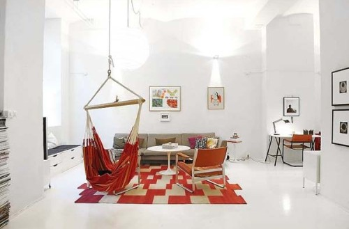 A white spacious room with a red geometric rug and a fun red hammock.