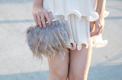 Sea-wave ruffled skirt and feather clutch.
