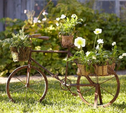 Upcycled Bicycle  Don't let that rusty bicycle or wheelbarrow go to waste, taking up space in your garage.  Instead, roll it into the garden and upcycle it as a planter, like this one featured a while back in Pottery Barn. Even if the bike or barrow isn't exactly antique, a coat or two of matte brown spray paint will easily cover any bright colors or brand names.  You can use sturdy wire (like an untwisted clothes hanger) to wrap around pots and attach them to the bike.  The wheelbarrow option is easiest because you can plant directly in it.